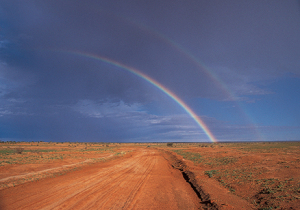 A double rainbow goes over an outback track